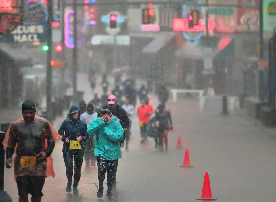 <strong>Runners struggle through the heavy rain on Beale Street. Organizers said that more than 2,000 participated out of the 5,000 who had registered.</strong>&nbsp;(Jim Weber/Daily Memphian)