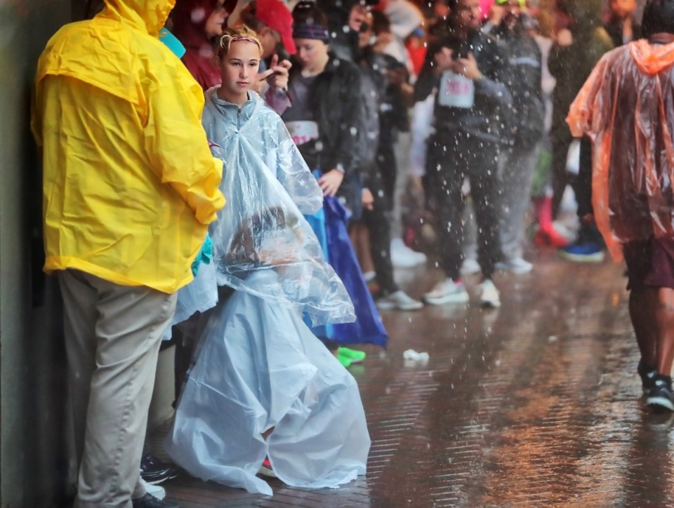 <strong>As the rain pours Downtown, Jorja Fowler (left) protects her friend Lacey Frey from the blowing rain.</strong> (Jim Weber/Daily Memphian)