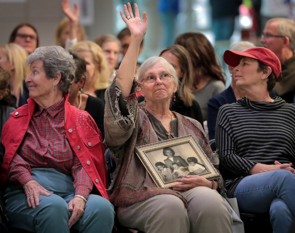 <strong>Holding a photo of her adoptive family from when she was a baby, Anne Stubblefield, 74, raises her hand when writers Lisa Wingate and Judy Christie call on victims of the Georgia Tann adoption scandal during a talk at the Benjamin L. Hooks Central Library on Oct. 26, 2019.</strong> (Jim Weber/Daily Memphian)