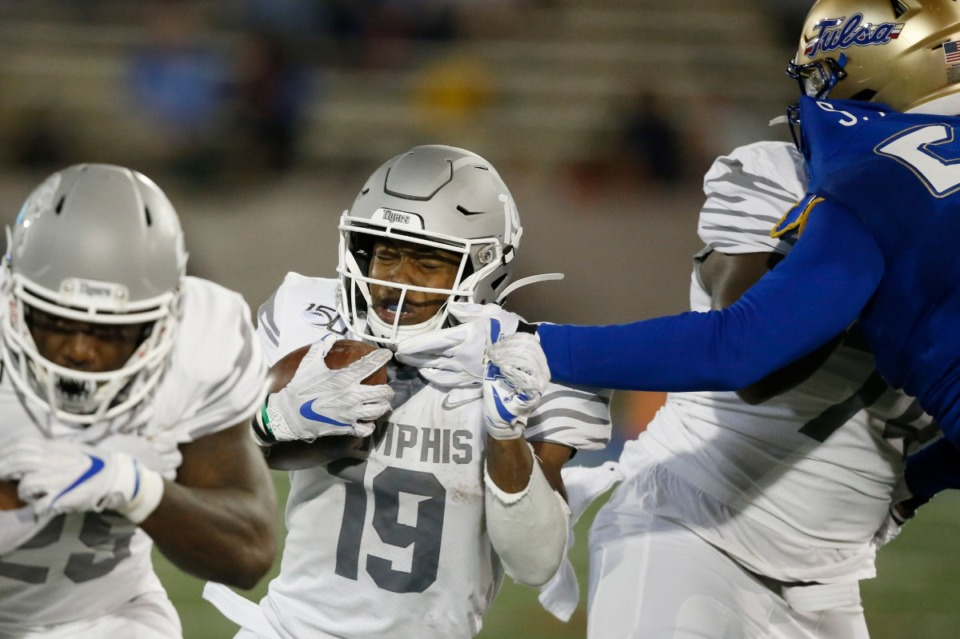 Memphis running back Kenneth Gainwell (19) has his face mask grabbed by a Tulsa defender as he carries in the first half of an NCAA college football game in Tulsa, Okla., Saturday, Oct. 26, 2019. The Golden Hurricane missed a last-second field goal to allow Memphis to escape with a 42-41 win. (AP Photo/Sue Ogrocki)