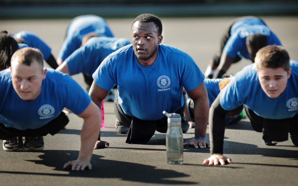 <strong>Recruit Brandon Jackson (center) keeps an eye on the training officer as Memphis police recruits work through two hours of physical training on Oct. 22 at the John Holt Police Training Academy. Like many police departments across the country, MPD is finding it difficult to recruit and retain new officers.</strong> (Jim Weber/Daily Memphian)