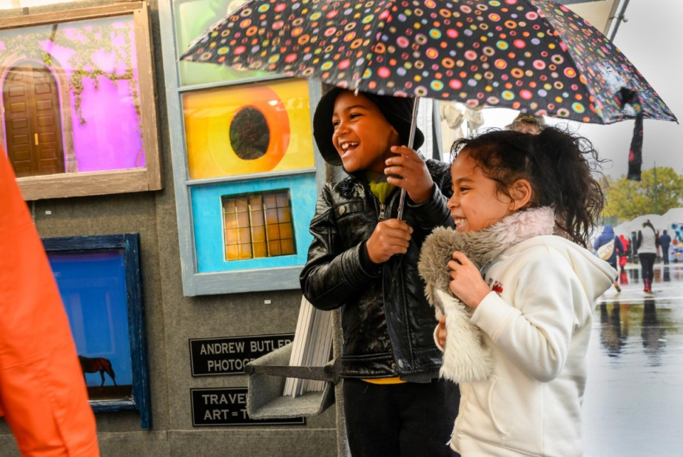 <strong>Massimo VanWinkle, 7, and Nathily Haynes, 5, enjoy the rain at the River Arts Festival on Riverside Drive Saturday, October 26, 2019.</strong> (Greg Campbell/Special for The Daily Memphian)
