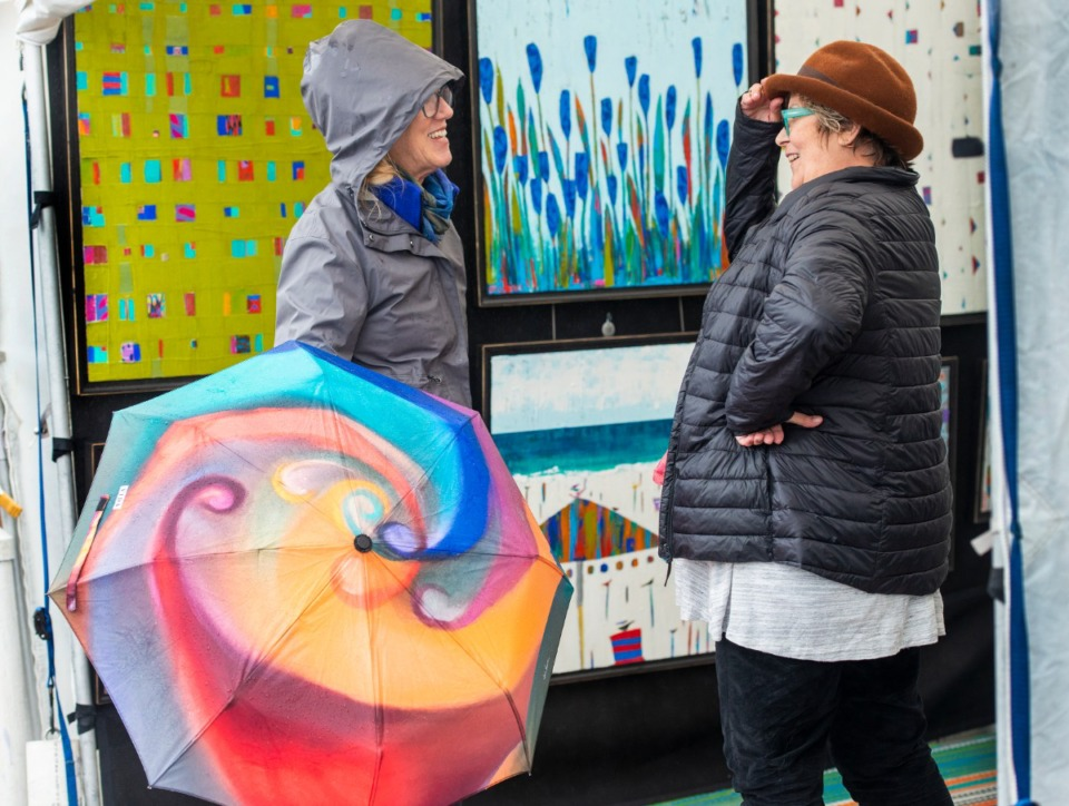 <strong>Diane French holds an umbrella with her original art work printed on it as she talks with fellow artist Debo Groover durning a lull in the crowd at the River Arts Festival on Riverside Drive Saturday, October 26, 2019.</strong> (Greg Campbell/Special for The Daily Memphian)