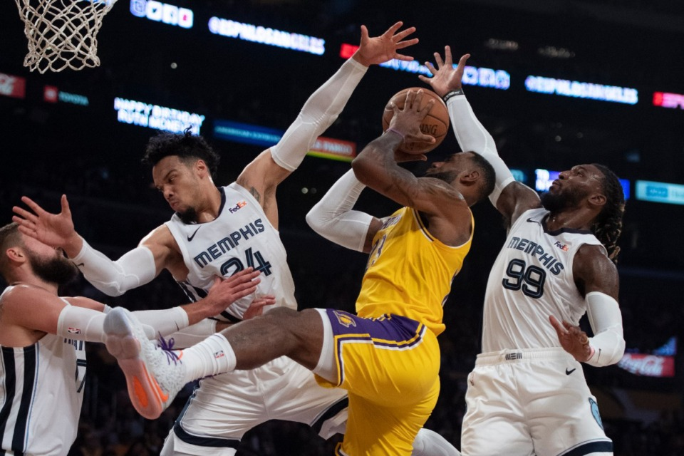<strong>Los Angeles Lakers forward LeBron James, center, shoots under pressure as Memphis Grizzlies guard Dillon Brooks, left, and forward Jae Crowder defend in an NBA basketball game in Los Angeles Oct. 29.</strong> (Kyusung Gong/AP)
