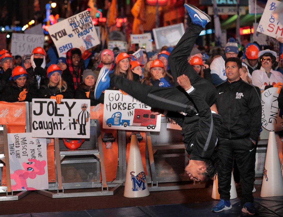"""<strong>A Memphis cheerleader performs for the crowd in the early morning as Tigers football fans pack Beale Street during the live broadcast of ESPN's """"College GameDay"""" on Nov. 2, 2019.</strong> (Jim Weber/Daily Memphian)"""