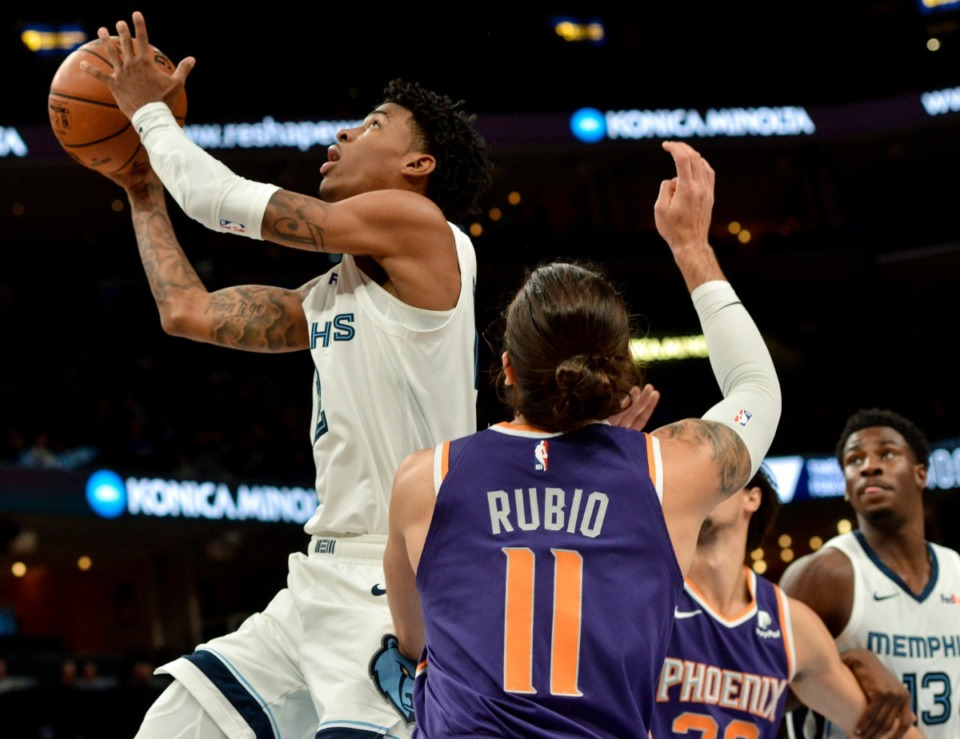 <strong>Memphis Grizzlies guard Ja Morant, left, shoots ahead of Phoenix Suns guard Ricky Rubio (11) in the first half of an NBA basketball game Saturday, Nov. 2, 2019, in Memphis, Tenn.</strong> (AP Photo/Brandon Dill)