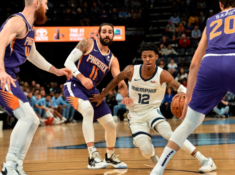 <strong>Memphis Grizzlies guard Ja Morant (12) handles the ball between Phoenix Suns center Aron Baynes, left, guard Ricky Rubio (11), and forward Dario Saric (20) in the first half of an NBA basketball game Saturday, Nov. 2, 2019, in Memphis, Tenn.</strong> (AP Photo/Brandon Dill)
