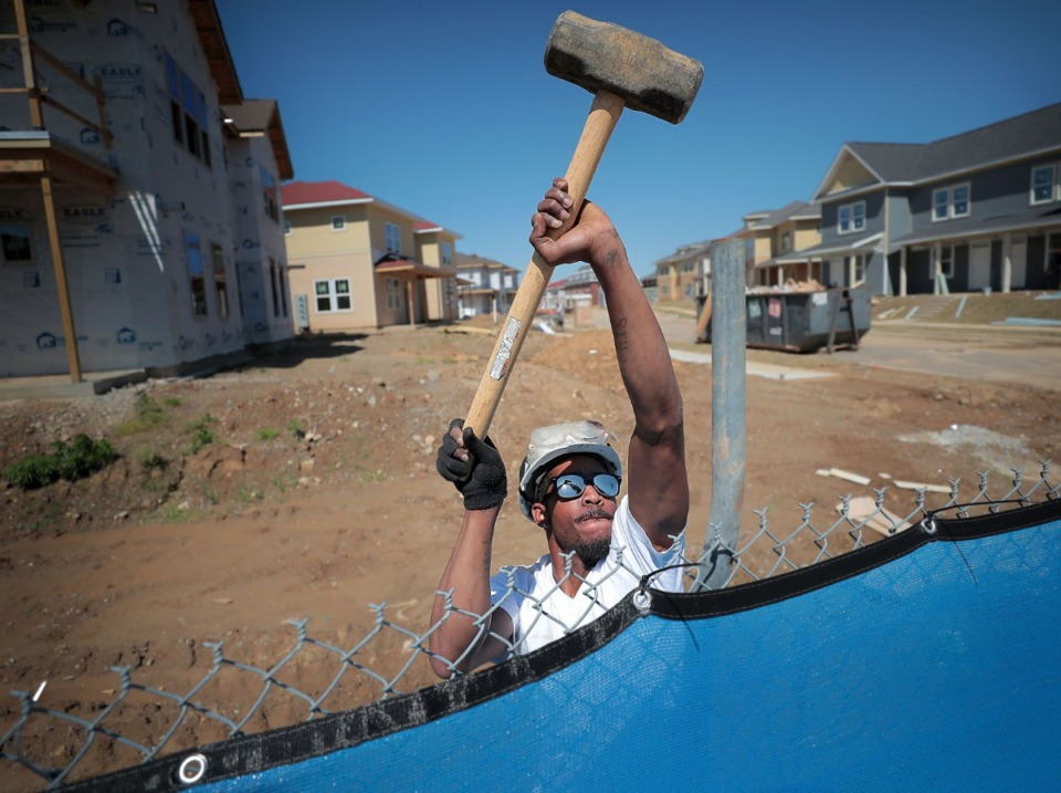 <strong>Arrhenius Eggleston anchors a security fence surrounding the first phase of the new mixed-income South City neighborhood April 26. More building permits at the former Foote Homes public housing site have been filed by the Memphis Housing Authority.</strong> (Jim Weber/Daily Memphian)
