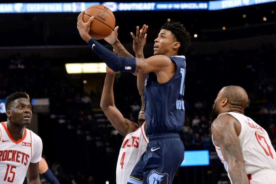 <strong>Grizzlies guard Ja Morant shoots between Houston Rockets center Clint Capela (15), and forwards Danuel House Jr. (4) and P.J. Tucker (17) Nov. 4.</strong> (Brandon Dill/AP)