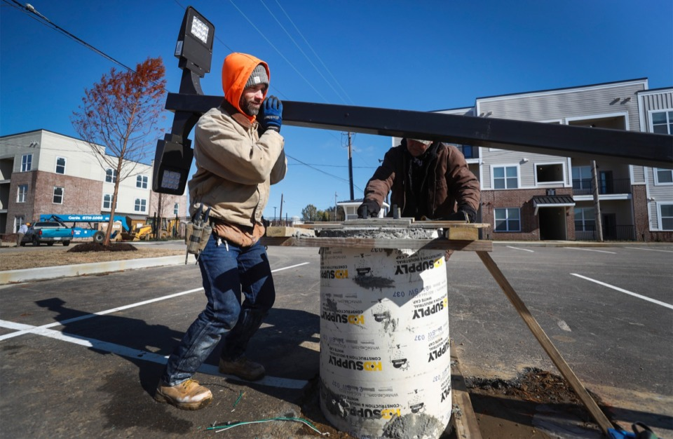 <strong>Benjamin Harris (left) holds a post while a team from A-C Electrical installs parking lot lights as construction continues at Forum Flats Nov. 12.</strong>&nbsp;(Mark Weber/Daily Memphian)