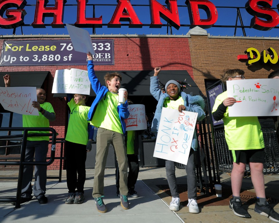 <strong>The kids of University Middle School's sixth grade class can barely hold in their excitement (and hot chocolate) when a passing car acknowledged them with its horn while the kids were out raising awareness for pedestrian safety in the area at the intersection of Walker Avenue and Highland Street the morning of Nov. 16. 2019.</strong> (Patrick Lantrip/Daily Memphian)