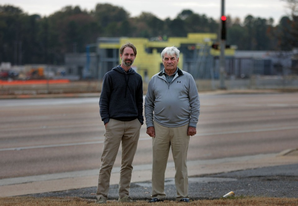 <strong>Hunter Smith (left) and his father, Wise Smith, stand on the empty site of their proposed Marketplace at Raleigh development, which is in the shadows of the larger Raleigh Springs Town Center that can be seen under construction in the background on Nov. 14, 2019. The Smiths credited the $45 million Raleigh Springs Town Center revitalization project with helping make their investment feasible.</strong> (Patrick Lantrip/Daily Memphian)