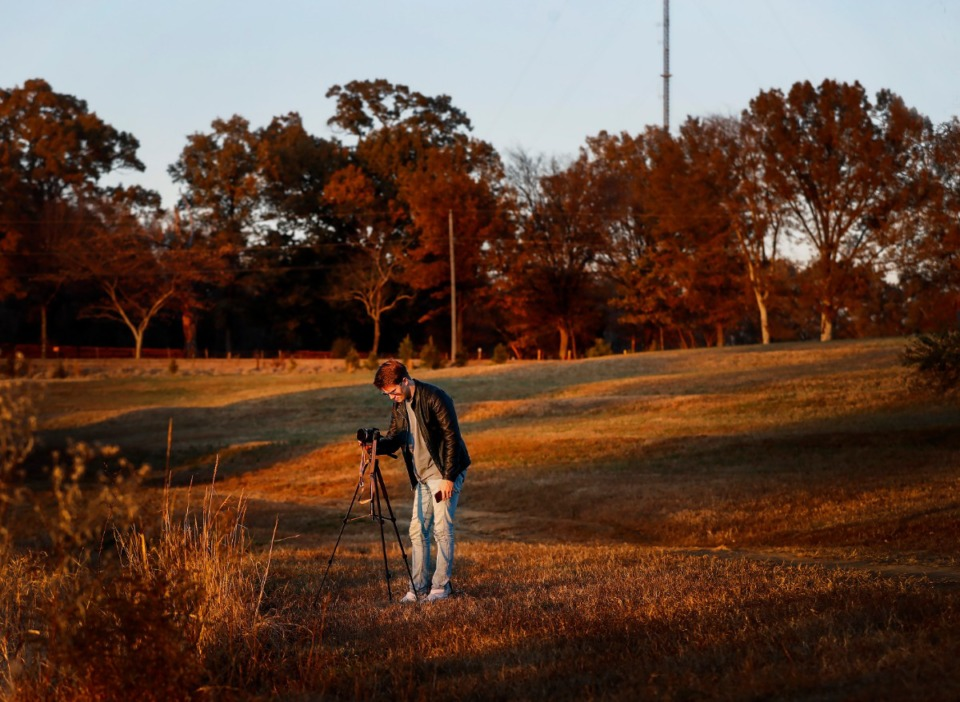 <strong>Austin Rich lines up his camera for a sunset photo in Shelby Farms. Behind the fall-colored tree line, across Raleigh Lagrange Road, will be the site of the new Velo at Shelby Farms apartments.</strong> (Mark Weber/Daily Memphian)