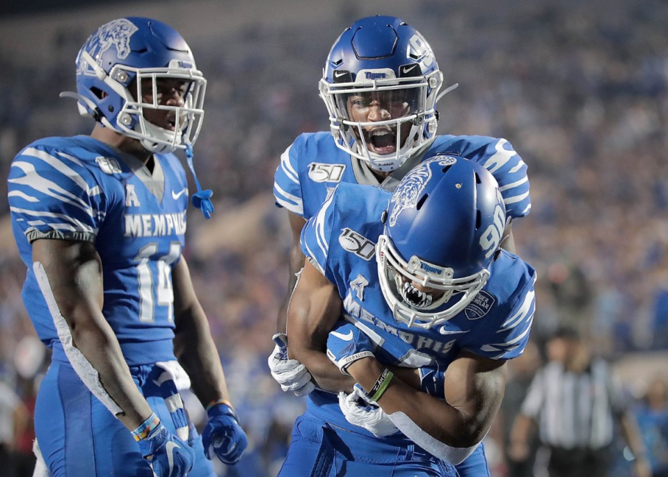 University of Memphis receiver Calvin Austin III (bottom) celebrates a touchdown with Damonte Coxie and Antonio Gibson (left) during the Tiger's game on Oct. 19, 2019 against the Tulane Green Wave at Liberty Bowl Memorial Stadium in Memphis. (Jim Weber/Daily Memphian)