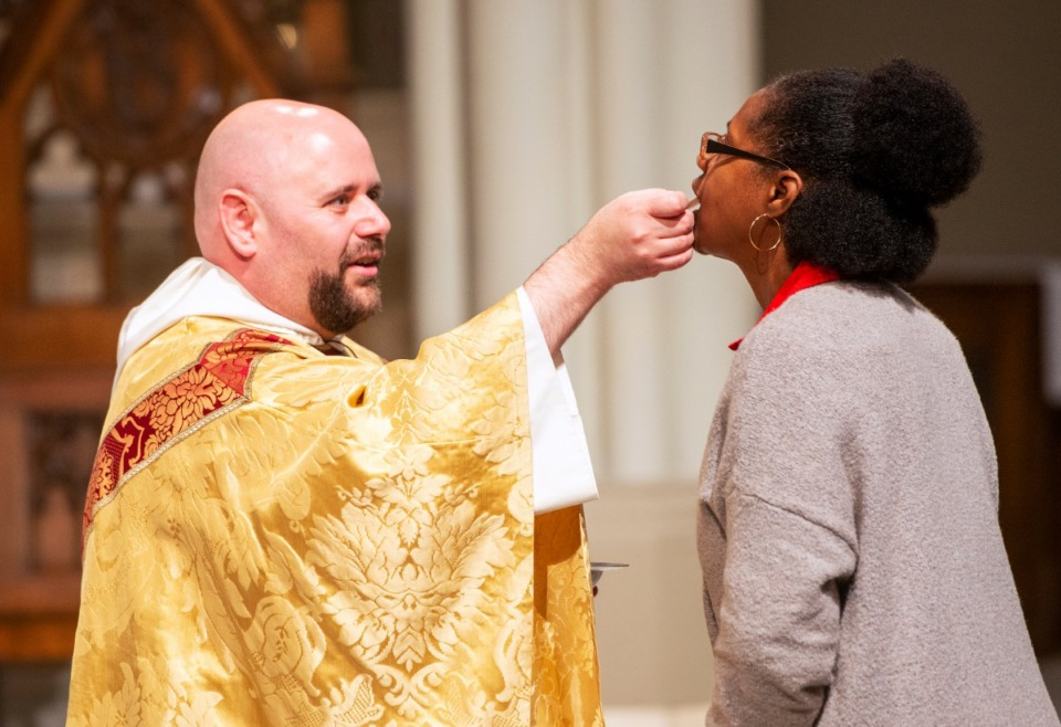 <strong>Father Augustine DeArmond serves communion to Cheryl O'Bannon at Mass observing the 180th anniversary of the first Catholic mass in Memphis, Nov. 17, 2019 at St. Peter Church</strong> (Greg Campbell/Special to The Daily Memphian)