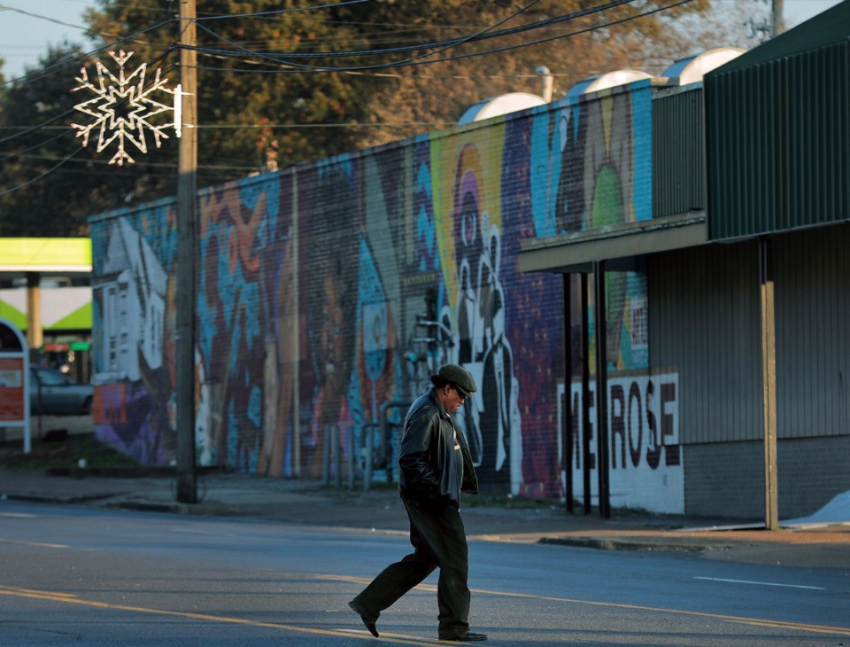 <strong>A man crosses Park Avenue the evening of Nov. 15, 2019, near one of the 50 lighted snowflakes that will adorn the avenue, thanks to a Shelby County Commission grant for Orange Mound.</strong> (Patrick Lantrip/Daily Memphian)