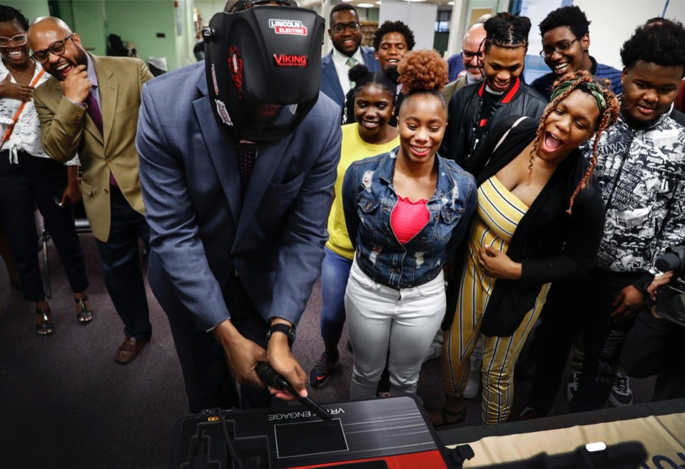 <strong>Martin Luther King College Prep students (right) and onlookers laugh as Shelby County Mayor Lee Harris (middle) attempts to use a virtual welding machine during a demonstration Nov. 19. Shelby County Government and Frayser Community Schools are partnering to host a pilot after-school program to allow high school students to complete two different certification programs. Students who complete the program will receive $1,000 vocational-technical scholarship from the county.</strong> (Mark Weber/Daily Memphian)
