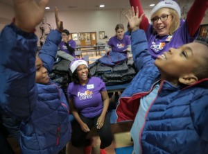 <strong>FedEx employees Rodrika Thompson (center) and Patricia Cranston help classmates D'Nero Shields (left) and Kentarius Carpenter pick out matching coats as kids try on their new coats from Operation Warm, which distributes winter coats to children at schools around the country, during a giveaway in conjunction with FedEx at Bruce Elementary School on Nov. 22, 2019.</strong> (Jim Weber/Daily Memphian)