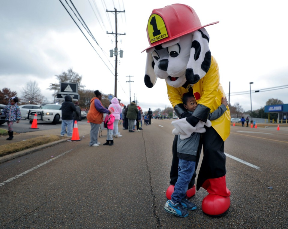 <strong>A mascot for the Memphis Fire Department hugs a child during the Memphis Christmas Parade in Whitehaven.</strong> (Patrick Lantrip/Daily Memphian)