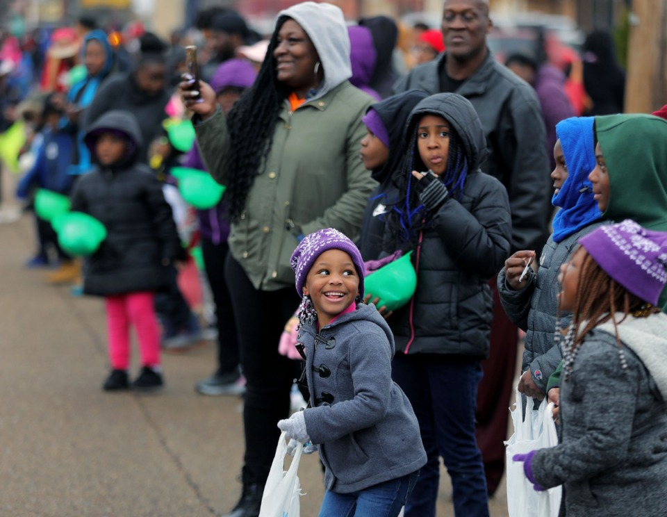 <strong>Smiling children line Elvis Presley Boulevard eager for sweet treats and a good seat to watch the Memphis Christmas Parade.</strong> (Patrick Lantrip/Daily Memphian)