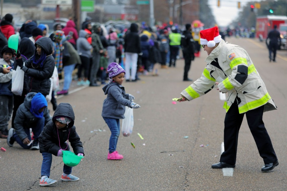 <strong>Members of the Memphis Fire Department hand out candy during the Memphis Christmas Parade.</strong> (Patrick Lantrip/Daily Memphian)