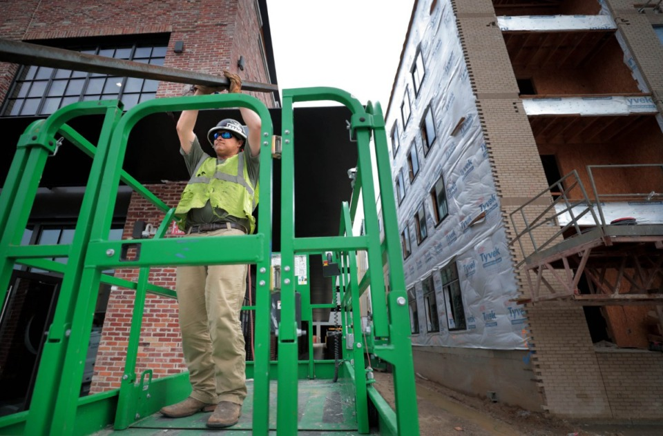 <strong>Michael Durham works on improvements to the facade of the former Wonder Bread factory as, next door, construction continues on The Rise apartment complex on Monroe part of the rapid revitalization efforts in the Edge District.</strong> (Jim Weber/Daily Memphian)
