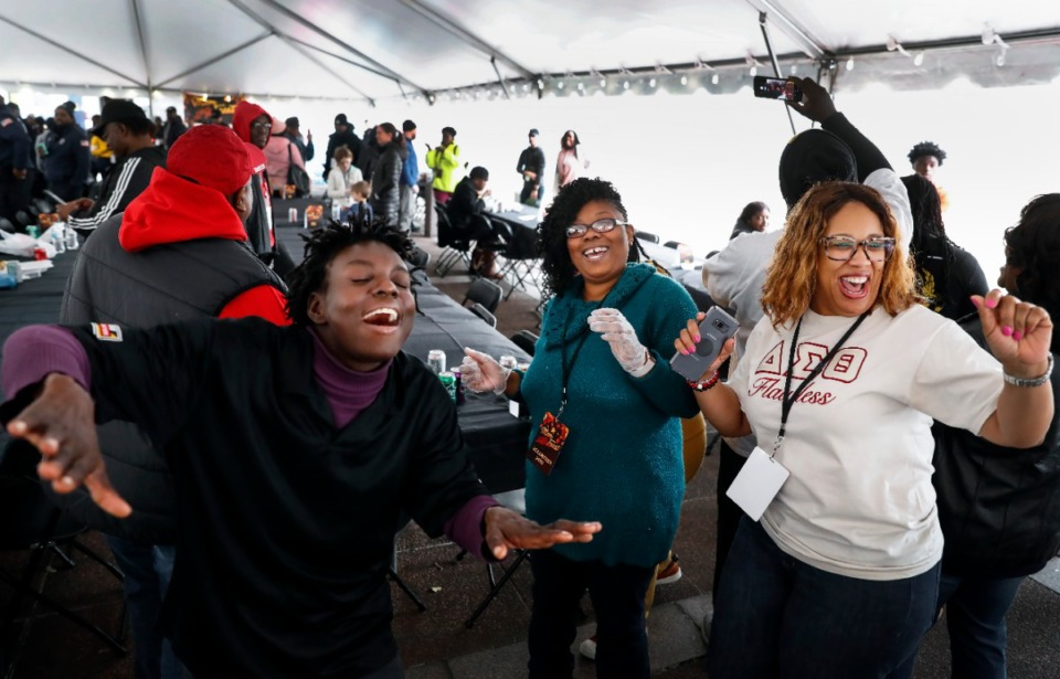 <strong>Angela Houston (left) dances with volunteers Ebony Rucker (center) and TeNita Freeman (right) during&nbsp; MemFeast, a Thanksgiving meal for the homeless Thursday, Nov. 28, 2019 at City Hall.</strong> (Mark Weber/Daily Memphian)