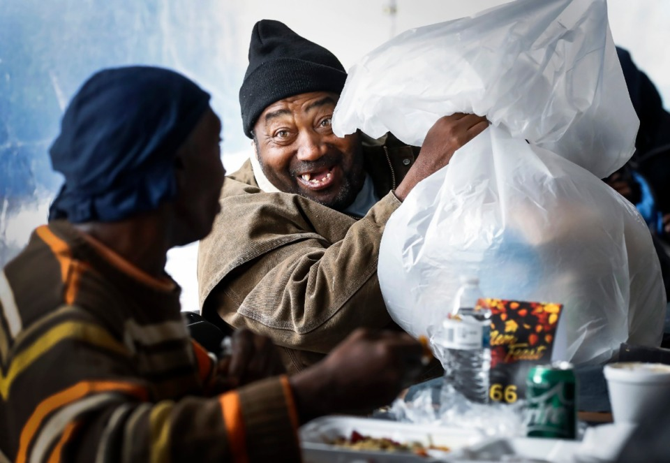 <strong>Willie Douglas (middle) smiles while packing up leftovers during MemFeast, a Thanksgiving meal for the homeless, on Thursday, Nov. 28, 2019.&nbsp;</strong>(Mark Weber/Daily Memphian)&nbsp;