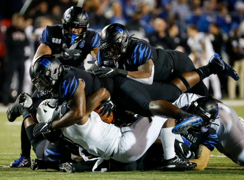 <strong>Memphis defender Morris Joseph (top) tackles Cincinnati running back Michael Warren II (bottom) for a loss Nov. 29 at Liberty Bowl Memorial Stadium.</strong> (Mark Weber/Daily Memphian)