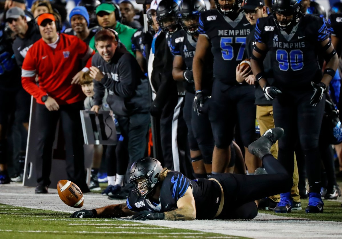 <strong>Memphis defender Jonathan Wilson (bottom) tries to stop a fumble from going out of bounds in the Nov. 29 game against Cincinnati.</strong> (Mark Weber/Daily Memphian)