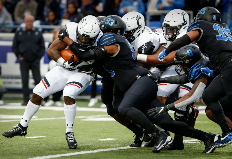 <strong>Memphis defender Desmond Hawkins (middle) tackles Cincinnati running back Michael Warren II (left) Nov. 29 at Liberty Bowl Memorial Stadium.</strong> (Mark Weber/Daily Memphian)