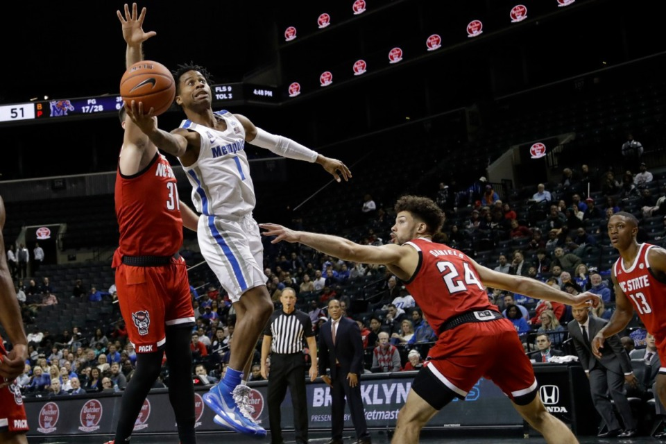 <strong>Memphis' Tyler Harris (1) drives past North Carolina State's Pat Andree (31) and Devon Daniels (24) during the first half of an NCAA college basketball game Thursday in the Barclays Classic in New York.</strong> (Frank Franklin II/AP)