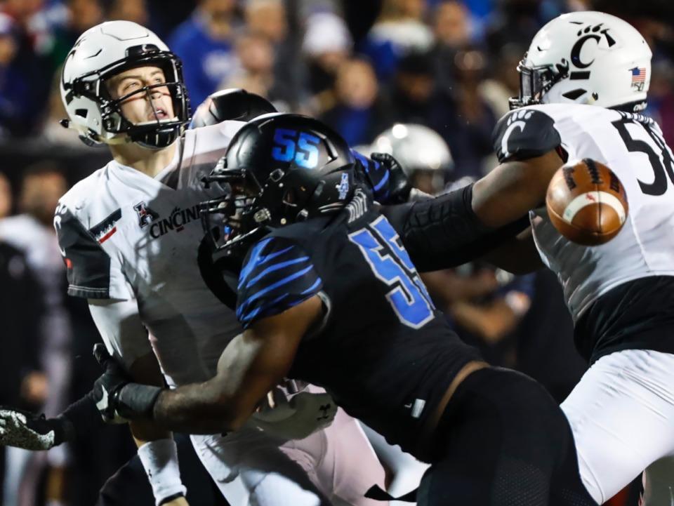 <strong>Memphis defender Bryce Huff (55) causes a fumble while sacking Cincinnati quarterback Ben Bryant (left) Nov. 29 at Liberty Bowl Memorial Stadium.</strong> (Mark Weber/Daily Memphian)