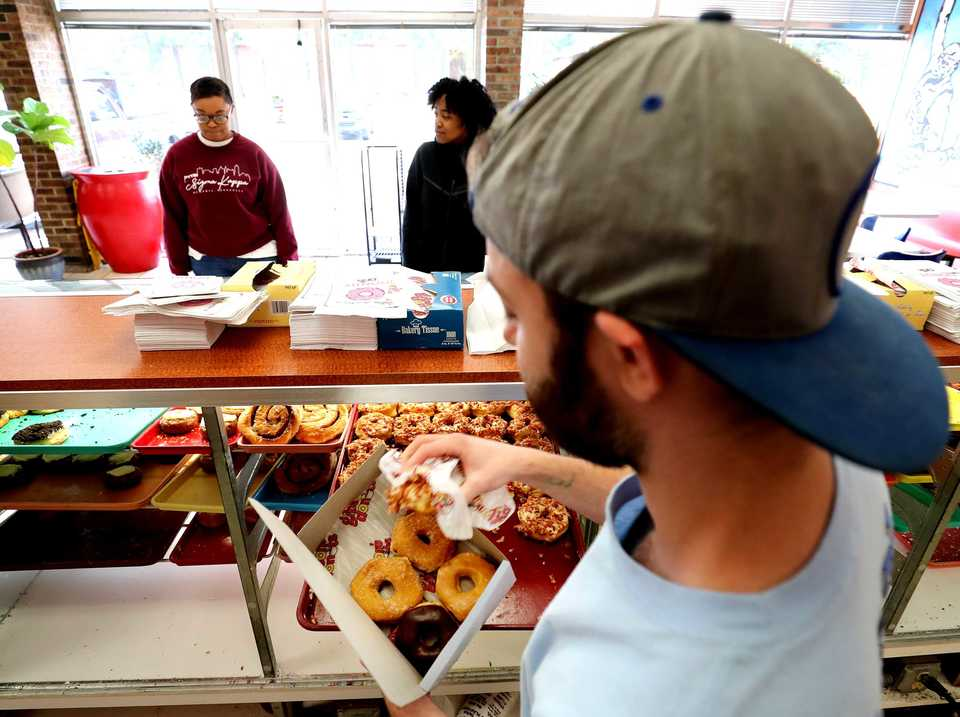 <strong>Michael Barrella fills up a box of donuts for customers at Gibson's Donuts on Monday, Nov. 5. The shop is expanding its kitchen for the second time in less than three years.</strong> (Houston Cofield/Daily Memphian.)