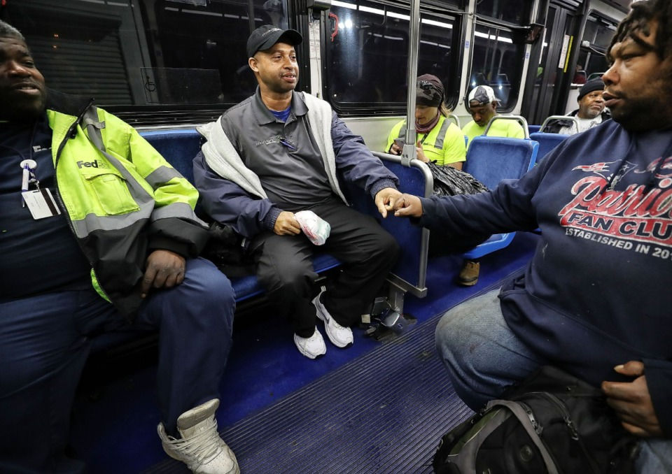 <strong>Sammie Hunter greets his friend and fellow bus rider Sean Huff during their morning commute on the #30 Brooks Peebles route. Hunter, who lives in Southeast Memphis and works at Methodist South, commutes almost 8 hours a day on the bus.</strong> (Jim Weber/Daily Memphian file)
