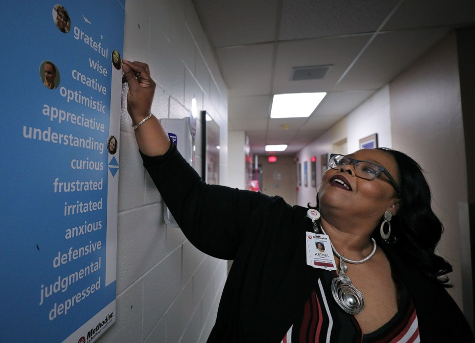 "<strong>Katina Clear, development assistant and data coordinator with Methodist Le Bonheur Healthcare's Organizational Effectiveness Department, adjusts her spot on the ""Mood Elevator"" she posted for her department Dec. 5, 2019. Clear, who is also taking classes at the University of Memphis, is able to advance her education thanks to a new program recently enacted by Methodist.</strong> (Patrick Lantrip/Daily Memphian)"