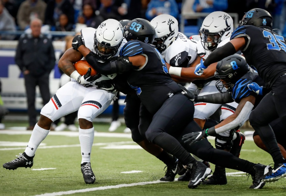 <strong>Memphis defender Desmond Hawkins (middle) tackles Cincinnati running back Michael Warren II (left) in the back field during action Friday, Nov. 29.</strong> (Mark Weber/Daily Memphian)