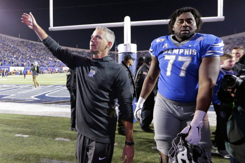 <strong>Mike Norvell waves to fans as he leaves the field with offensive lineman Obinna Eze (77) after the team's Nov. 2 victory over SMU.</strong>&nbsp;(Mark Humphrey/AP)