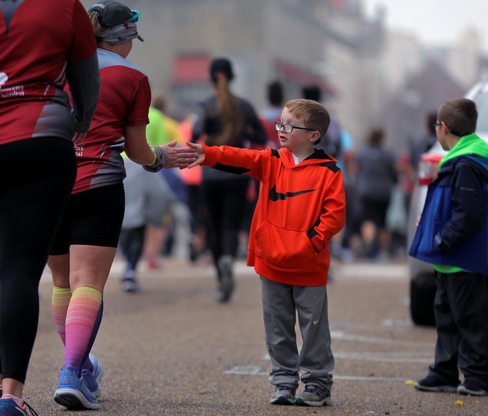 <strong>Owen Reed high fives runners in the St. Jude Marathon as they make their way through Downtown Memphis on Dec. 7, 2019.</strong> (Patrick Lantrip/Daily Memphian)