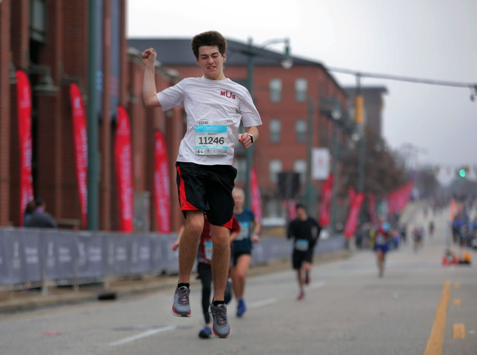 <strong>Memphis University School senior Henry Bridgforth jumps over the finish line with excitement after completing a half marathon at the St. Jude Marathon in Downtown Memphis on Dec. 7, 2019.</strong> (Patrick Lantrip/Daily Memphian)