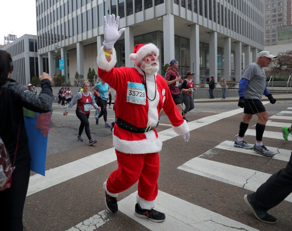 <strong>A runner dressed as Santa waves to the crowd during the St. Jude Marathon in Downtown Memphis on Dec. 7, 2019.</strong> (Patctk Lantrip/Daily Memphian)