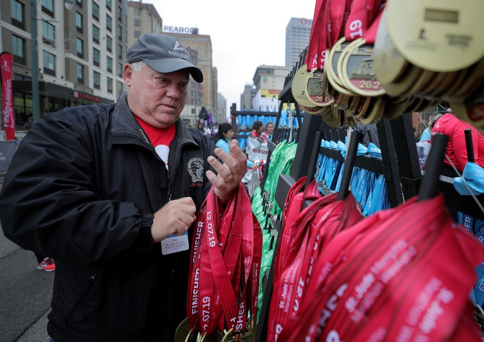 <strong>Travis Dollar gathers an armful of medals from the rack during the St. Jude Marathon in Downtown Memphis on Dec. 7, 2019.</strong> (Patctk Lantrip/Daily Memphian)