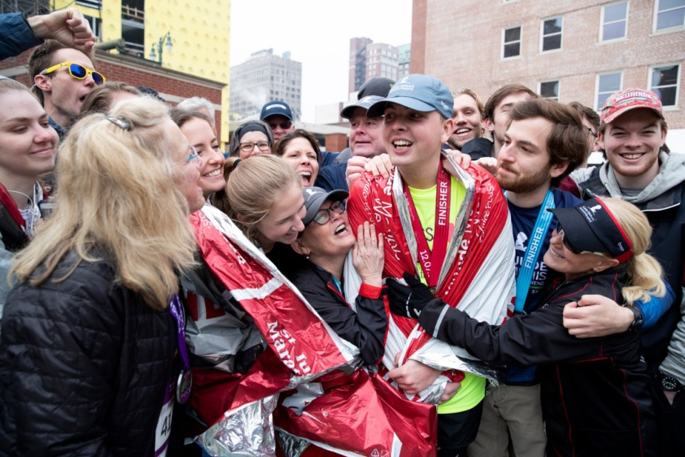 <strong>St. Jude patient Adam Cruthirds is embraced by members of his fundraising and support team after he completed the annual St. Jude Memphis Marathon.</strong> (Mike Brown/St. Jude.)