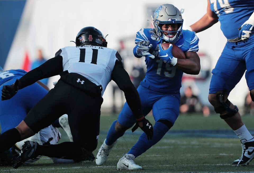<strong>University of Memphis running back Kenneth Gainwell looks for an opening under pressure by Cincinnati's Leonard Taylor (11) during a run in the first half of the Tiger's AAC Championship game on Dec. 7, 2019, against the Bearcats at the Liberty Bowl Memorial Stadium.</strong> (Jim Weber/Daily Memphian)