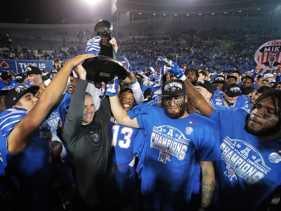 <strong>Former University of Memphis head coach Mike Norvell (left) celebrates with the team after the Tigers beat Cincinnati to win the AAC Championship game on Dec. 7, 2019, at the Liberty Bowl Memorial Stadium.</strong> (Jim Weber/Daily Memphian)