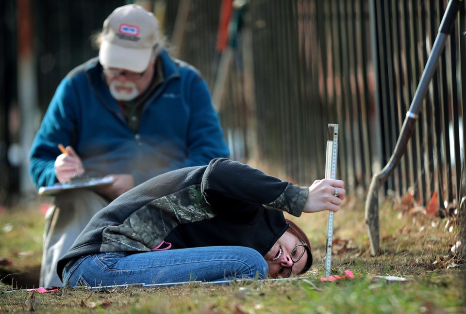 <strong>Abbi Vanaman, with Memphis Housing and Community Development, helps archaeologist Guy Weaver (left) during archaeological testing on Dec. 12 at the Deaderick Family Cemetery in Orange Mound, which may be much larger than the small plot that is there now. Investigators believe that the cemetery may include the burial sites of slaves from the Deaderick Plantation.</strong> (Jim Weber/Daily Memphian)