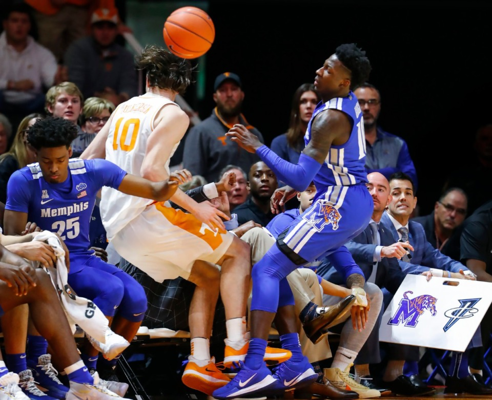 <strong>Tennessee forward John Fulkerson (left) falls into the Memphis bench after battling Tiger guard Damion Baugh (right) for a loose ball during action Saturday, Dec. 14, 2019 in Knoxville, Tennessee.</strong> (Mark Weber/Daily Memphian)