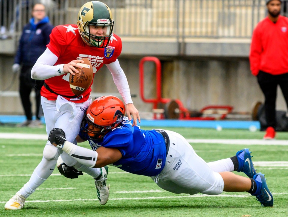 <strong>Red team quarterback Cole Putnam of FACS tries to break away from Blue team's Cody Daniels from Ridgeway at the Liberty Bowl High School All-Star game on Dec. 14, 2019, at MUS.</strong> (Greg Campbell/Special to The Daily Memphian)