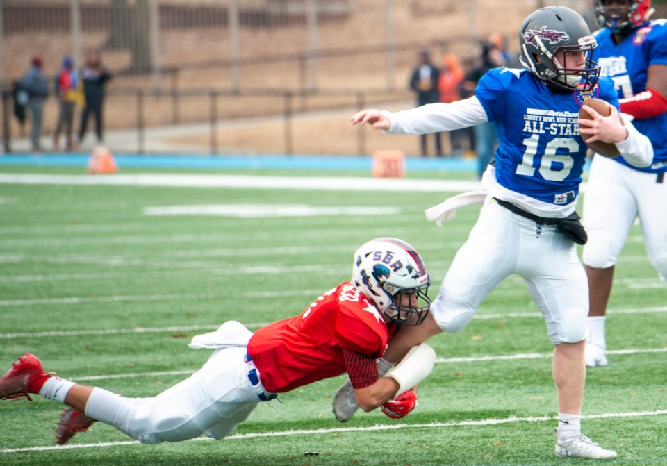 <strong>Red team defensive back Dante Carrasco from St. Benedict grabs the leg of Blue team quarterback Mitch Austin from Collierville at the Liberty Bowl High School All-Star&nbsp;&nbsp;game on Dec. 14, 2019, at MUS.</strong>&nbsp;(Greg Campbell/Special to The Daily Memphian)