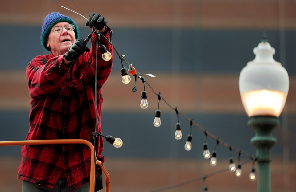 <strong>As the two-year anniversary of the removal of Confederate monuments from two city parks approaches, Ronnie MaCarty hangs festive lights at Memphis Park on Dec. 17 in preparation for a Christmas market on Friday, Dec. 20.</strong> (Jim Weber/Daily Memphian)